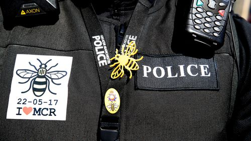 A police officer wears a bee, which has become a symbol of unity since the attack. (AAP)