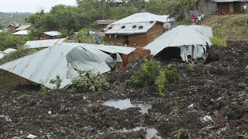 Damaged houses near the area where two houses were crushed by the collapse of a massive, sprawling dumpsite that hit just after midnight when rains poured in Pemba city on the northeastern coast of Mozambique.