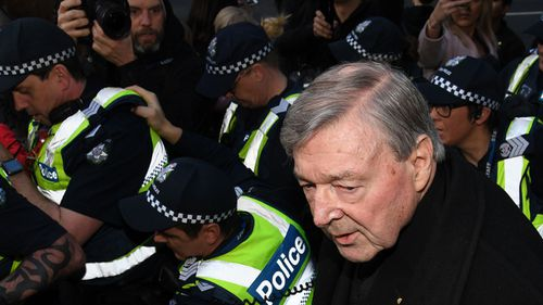 Officers created a human barricade between Pell and a mob of media outside his first court appearance. (AAP)