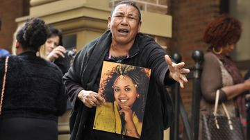 The mother of Ethiopian woman Wubanchi Asfaw, who was stabbed to death in Sydney in 2014, holds a photo after her husband was convicted of manslaughter.