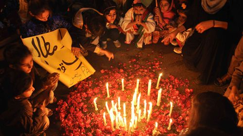 Pakistani people light candles to pray for the victims of the Taliban school massacre. (AAP)