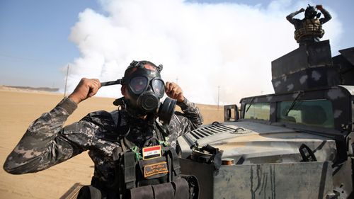 Iraqi forces wear gas masks for protection as smoke billows in the background after Islamic State (IS) group jihadists torched Mishraq sulphur factory, about 30 kilometres south of Mosul. Toxic fumes released when jihadists torched a sulphur plant near Mosul have killed two Iraqi civilians, made many ill and forced US troops at a nearby base to wear masks.  AHMAD AL-RUBAYE / AFP