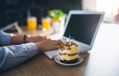 Office birthday cake while typing on a laptop computer at desk
