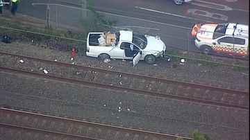 A white ute had been travelling west when it hit a fence and continued onto the tracks.