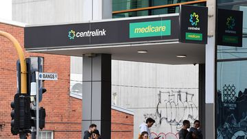 People are seen waiting in line at the Prahran Centrelink office in Melbourne, Tuesday, March 24, 2020.