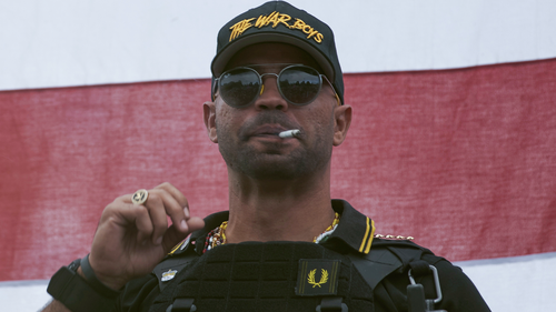Proud Boys leader Enrique Tarrio wears a hat that says The War Boys and smokes a cigarette at a rally in Delta Park on Saturday, Sept. 26, 2020, in Portland, Ore. (AP Photo/Allison Dinner)