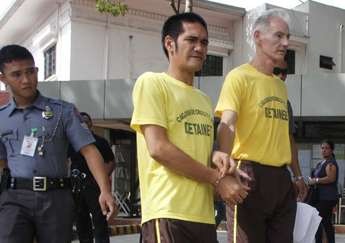 Peter Gerald Scully of Australia, right, walks in handcuffs with an unidentified detainee as they arrive at Cagayan de Oro city hall in southern Philippines on Tuesday, June 16, 2015. (AAP)