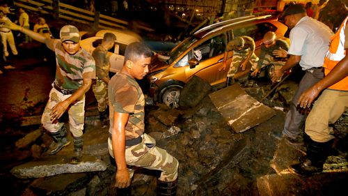 Rescue workers attempt to find survivors trapped under a collapsed bridge in Calcutta, India.