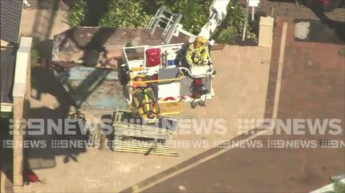 The worker, believed to be in his 20s, was said to have fallen through a roof baton and dropped more than two metres. Picture: 9NEWS.