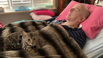 Mario the cat sits with Mr Boileau as he rests. He is in the end-stages of a cruel neurological disease.
