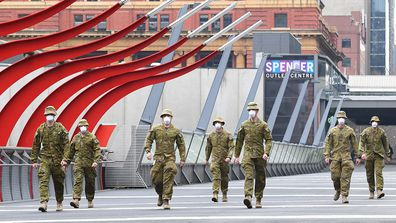 Members of the Australian Defence Force walk through Melbourne, which is now under stage four restrictions and a night curfew.