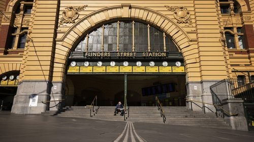A lone person reads a newspaper at Flinders Street Station in Melbourne.