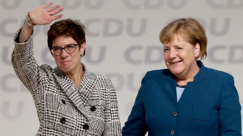 Annegret Kramp-Karrenbauer waves at members of the Christian Democratic Union after her election as the new leader, next to German Chancellor and outgoing CDU leader Angela Merkel.