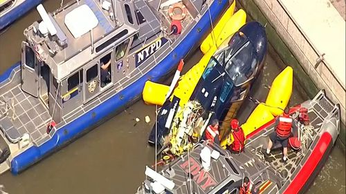 Screenshot from WABC-TV video shows units from the New York City police and fire departments work to secure a helicopter to the dock after it crashed in the Hudson River.