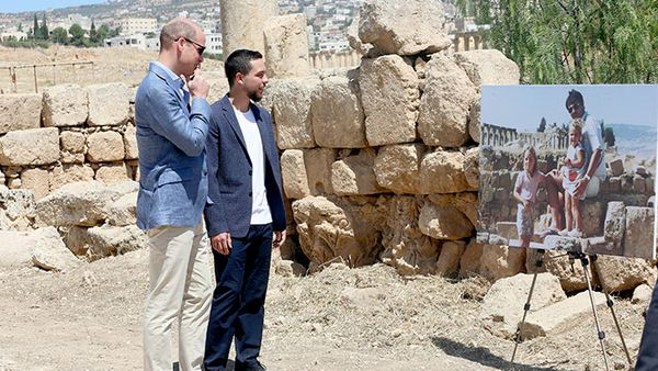 Prince William and Jordanian Crown Prince Hussein look at a photograph showing William's wife, the former Kate Middleton, her father Michael and younger sister Pippa in the ruins of the Roman city of Jerash in the 1980s. (AAP)