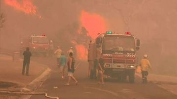 Fire truck in Australia with fierce blaze behind it.