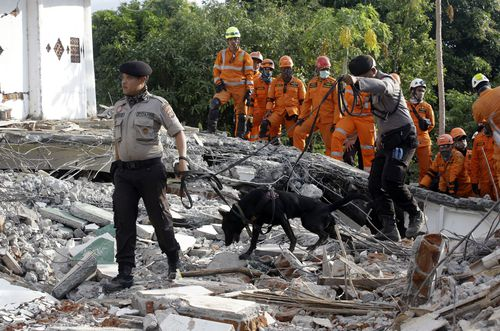 Concerns have been risen by local residents that rescuers looking for survivors are not able to work fast enough without heavy machinery. Picture: AP.