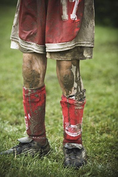 Child mud on his legs socks and boots following game.