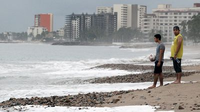 Locals survey the scene at Puerto Vallarta. (AAP)