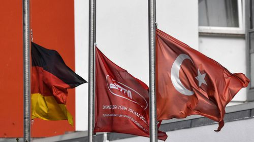German and Turkish flags hanging half-mast in front of a mosque after the shooting in Hanau, Germany, Friday, Feb. 21, 2020.