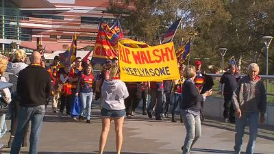 Crows supporters carried banners to the memorial service. (9NEWS)