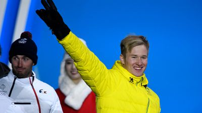 Jarryd Hughes of Australia gestures prior to receiving the silver medal for Snowboard Cross during a medal ceremony. (AAP)