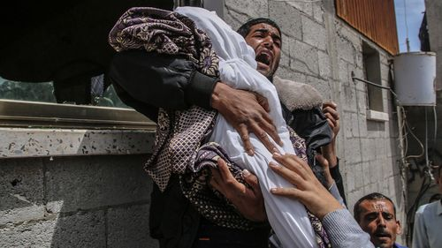 A Palestinian relative of a 14-month baby girl carries her body during her funeral.