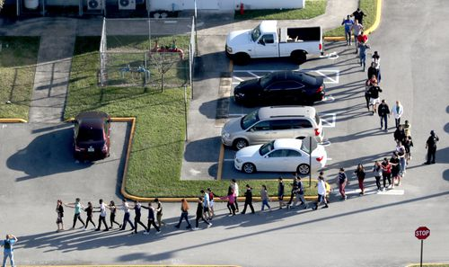 Students are led away from the classrooms by police at the height of the shootings. Picture: AAP