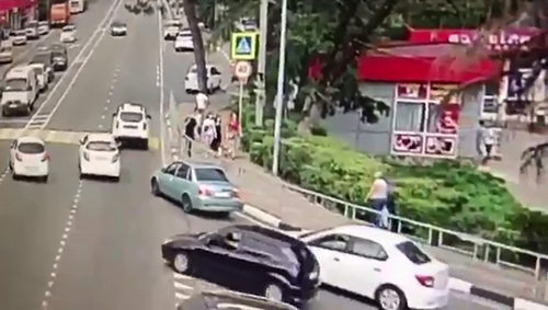The car first veers into the wrong lane towards a crowd of oblivious pedestrians.