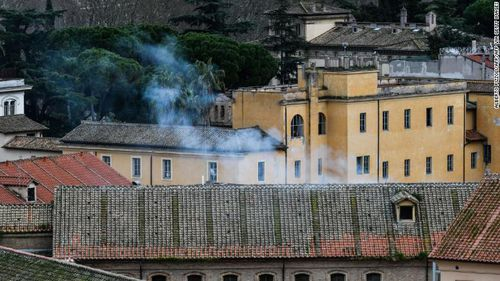 Smoke billows from a rooftop of the Regina Coeli prison in central Rome after protests in at least 22 prisons left 11 inmates dead.