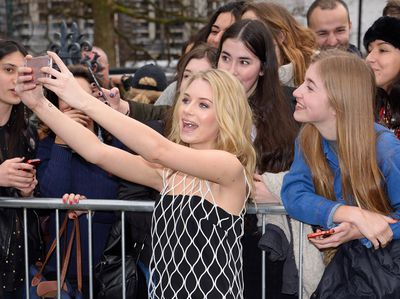 Lottie Moss, Kate Moss' younger sister, took a moment outside the Topshop show to snap selfies with fans.