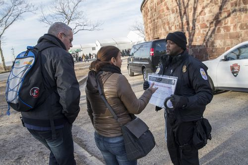 United States Park police officer Fernandez, right, informs tourists that the Statue of Liberty is closed. (AAP)