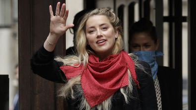 American actress Amber Heard smiles at the media as she arrives at the High Court in London, Thursday, July 23, 2020.