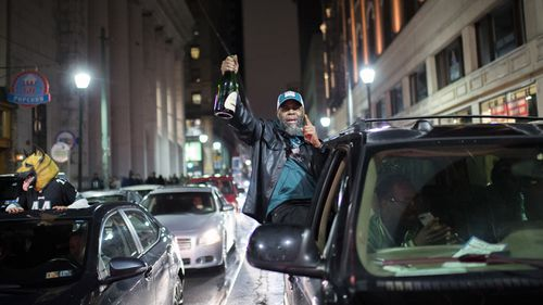 A Philadelphia Eagles fan holds a champagne bottle out a car window. (AAP)