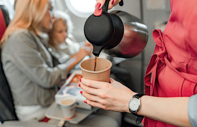 Flight attendant pouring a coffee during plane service