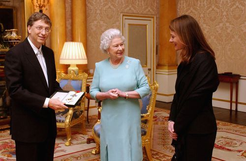 Queen Elizabeth II presents Bill Gates with an honorary knighthood in 2005, as his wife Melinda watches on.