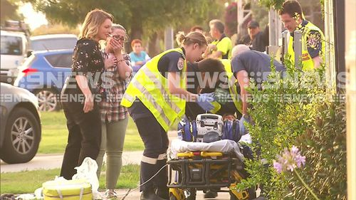 A woman cries as she watches paramedics care for the child. (9NEWS)