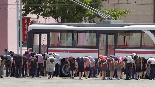 Pyongyang residents bow in memory of Kim Il-Sung on the 25th anniversary of his death.