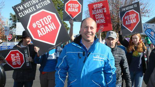 Josh Frydenberg trailed by Adani mine protesters on election day.