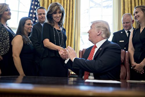 US President Donald J. Trump, right, shakes hands with Tammie Jo Shults, Co-captain of the flight, in the Oval Office in May.