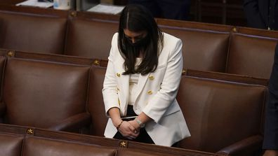 Rep. Alexandria Ocasio-Cortez, D-N.Y., bows her head during a closing prayer of a joint session of the House and Senate to confirm Electoral College votes at the Capitol, early Thursday, Jan 7, 2021, in Washington