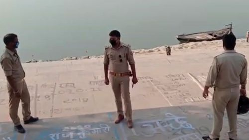 Police officials stand guard at the banks of the river where several bodies were found lying in Ghazipur district in Uttar Pradesh.