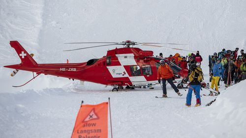 Rescue forces and helicopters search for missed persons after an avalanche swept down a ski piste in the central town of Andermatt.