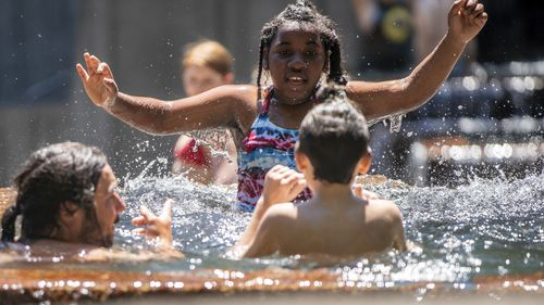 People gathered at Keller Fountain Park to take a dip and cool off, in Portland, Oregon.