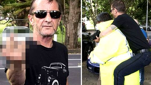 Phil Rudd playing up for the cameras outside court at an earlier appearance. (AAP)