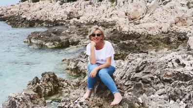 Susan Francis sitting on rocks on holiday