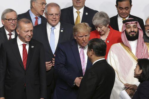 Prime Minister Scott Morrison looks on as President of the United States Donald Trump and President of China Xi Jinping shake hands during the 'family photo' at the G20 Summit in Osaka, Japan, in 2019.