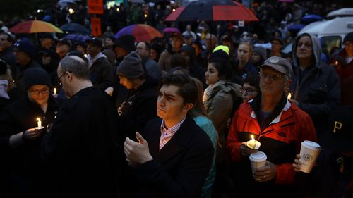 People hold candles as they gather for a vigil in the aftermath of a deadly shooting at the Tree of Life Synagogue