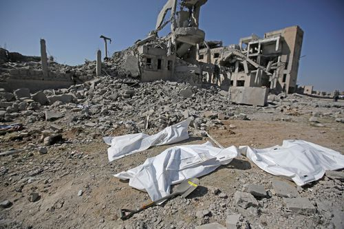 Bodies covered in plastic lie on the ground amid the rubble of a Houthi detention center destroyed by Saudi-led airstrikes.