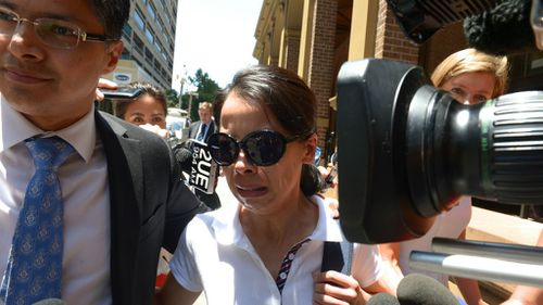 "A visibly distraught Kathy Lin, the wife of Lian Bin ""Robert"" Xie leaves the Supreme Court in December. (AAP)"